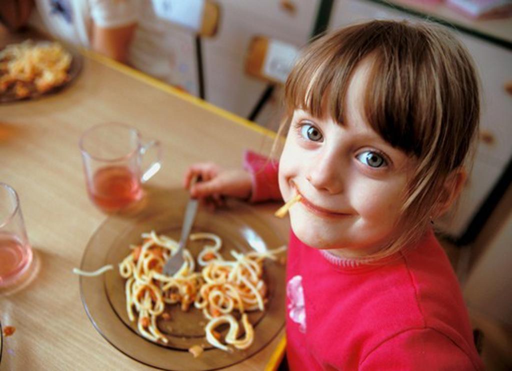Girl eating spaghetti : Stock Photo