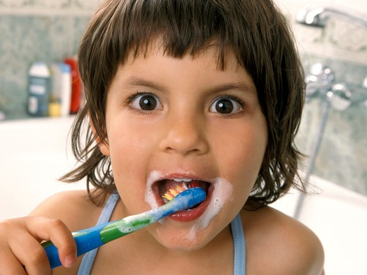 Girl brushing teeth in bathroom, big eyes : Stock Photo