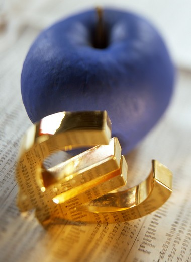 GLOWING GOLDEN 'EURO' CURRENCY LOGO AND A BLUE APPLE ON FINANCIAL PAPER. : Stock Photo