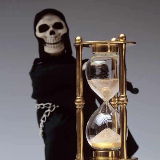 BRASS HOURGLASS IN FRONT OF THE GRIM REAPER. : Stock Photo