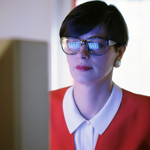 EXECUTIVE WOMAN'S FACE WITH COMPUTER SCREEN REFLECTED IN GLASSES : Stock Photo