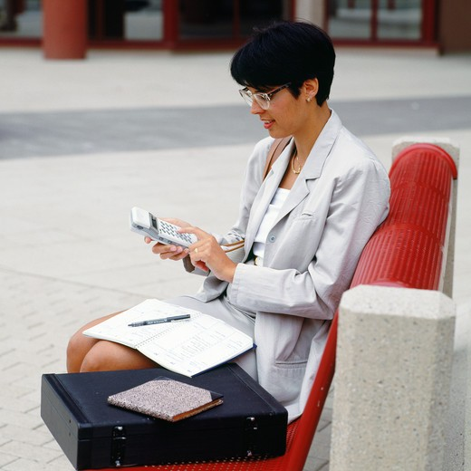 Stock Photo: 4285-6284 YOUNG BUSINESSWOMAN SITTING OUTSIDE ON A BENCH AND DIALING ON HER CELLULAR TELEPHONE