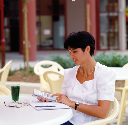 Stock Photo: 4285-6286 YOUNG BUSINESSWOMAN AT CAFE'S TERRACE DIALING ON HER CELLULAR TELEPHONE