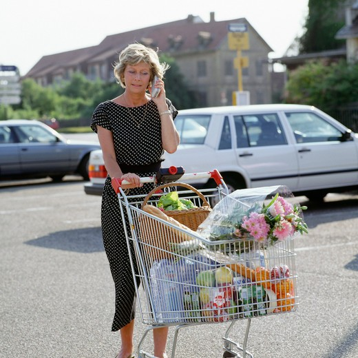Stock Photo: 4285-6297 MATURE WOMAN WITH SUPERMARKET SHOPPING CART AND CELLULAR TELEPHONE