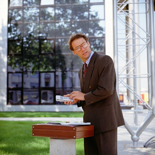 Stock Photo: 4285-6313 BUSINESSMAN WITH CELLULAR TELEPHONE IN FRONT OF OFFICE BUILDING