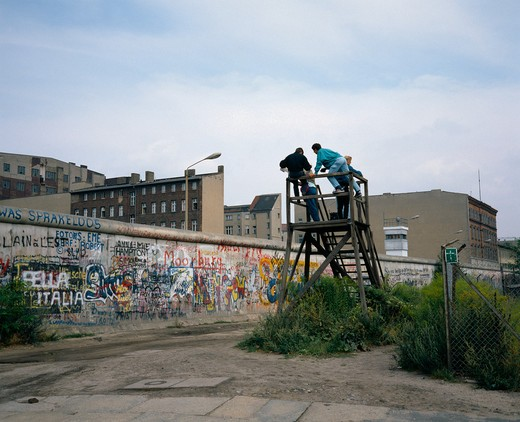 Stock Photo: 4285-6420 1986 GERMANY BERLIN WALL WITH GRAFFITI AND  PEOPLE ON OBSERVATION POST AT ZIMMERSTRASSE STREET
