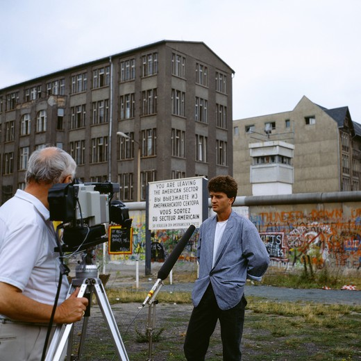 Stock Photo: 4285-6448 1986 GERMANY BERLIN TV INTERVIEW OF A FORMER EAST SOLDIER IN FRONT WALL WITH GRAFFITI AND WATCHTOWER AT ZIMMERSTRASSE STREET