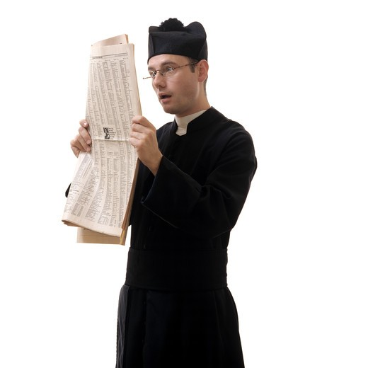 CATHOLIC PRIEST READING A FINANCIAL NEWSPAPER : Stock Photo