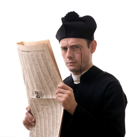 PORTRAIT OF A CATHOLIC PRIEST WITH A MONOCLE AND FINANCIAL NEWSPAPER : Stock Photo