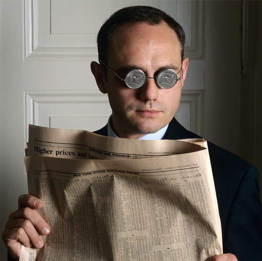 PORTRAIT OF A MAN WITH US DOLLAR COIN GLASSES AND FINANCIAL NEWSPAPER : Stock Photo