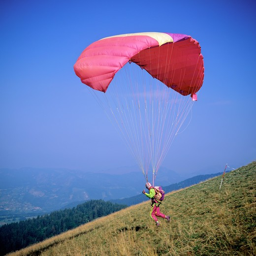FRANCE FRENCH ALPS SAVOIE PARAGLIDER TAKING OFF : Stock Photo