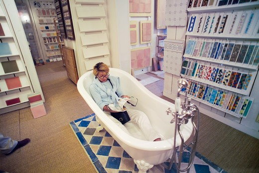 Stock Photo: 4285-8323 MR FRANCE BRITTANY RENNES WOMAN SHOPPING FOR A BATH IN A SHOWROOM MR MODEL RELEASED