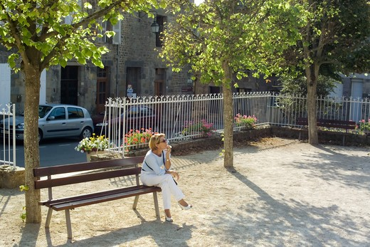 Stock Photo: 4285-8344 MR FRANCE BRITTANY BECHEREL VILLAGE CITE DU LIVRE BOOK CITY WOMAN RELAXING ON A BENCH MR MODEL RELEASED