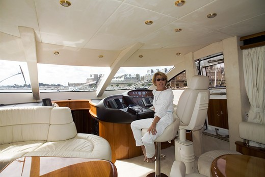 Stock Photo: 4285-8633 MR FRANCE BRITTANY INTERIOR OF A PRIVATE LUXURY YACHT AND WOMAN ON CAPTAIN'S SEAT
