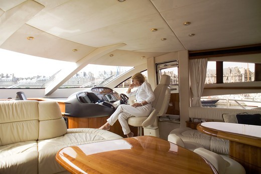Stock Photo: 4285-8634 MR FRANCE BRITTANY INTERIOR OF A PRIVATE LUXURY YACHT AND WOMAN ON CAPTAIN'S SEAT