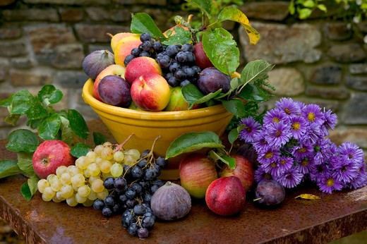 Stock Photo: 4285-8799 SEASONAL STILL LIFE WITH AN ASSORTMENT OF AUTUMNAL FRUITS IN A YELLOW BOWL AND ASTER FLOWERS