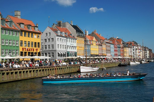 TOURIST TOUR BOAT ANCIENT HOUSES AND WATERFRONT CAFE TERRACES NYHAVN NEW HARBOUR COPENHAGEN DENMARK : Stock Photo