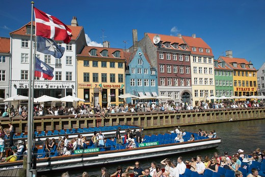 Stock Photo: 4285-9166 FLAGS TOURIST TOUR BOATS ANCIENT HOUSES AND WATERFRONT CAFE TERRACES NYHAVN NEW HARBOUR COPENHAGEN DENMARK