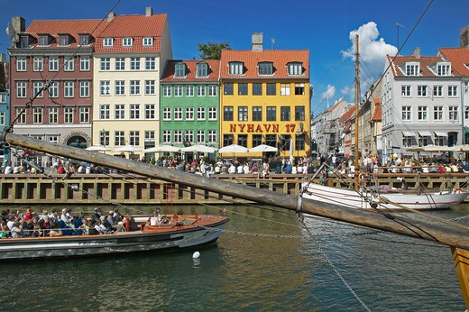 TOURIST TOUR BOAT ANCIENT HOUSES MOORED SAILBOATS AND WATERFRONT CAFE TERRACES NYHAVN NEW HARBOUR COPENHAGEN DENMARK : Stock Photo
