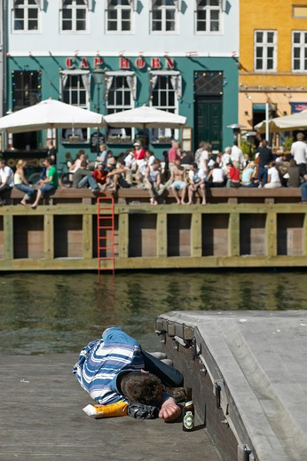 Stock Photo: 4285-9172 DRUNK MAN SLEEPING ON A BARGE ANCIENT HOUSES AND WATERFRONT CAFE TERRACE NYHAVN NEW HARBOUR COPENHAGEN DENMARK