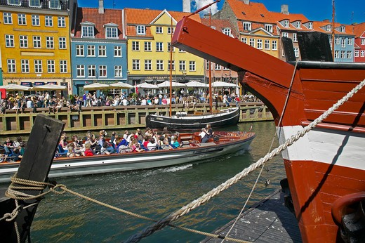 Stock Photo: 4285-9174 TOURIST TOUR BOAT MOORED SAILBOATS ANCIENT HOUSES AND WATERFRONT CAFE TERRACES NYHAVN NEW HARBOUR COPENHAGEN DENMARK