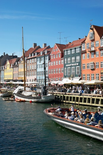 Stock Photo: 4285-9181 TOURIST TOUR BOAT MOORED SAILBOAT ANCIENT HOUSES AND WATERFRONT CAFE TERRACES NYHAVN NEW HARBOUR COPENHAGEN DENMARK