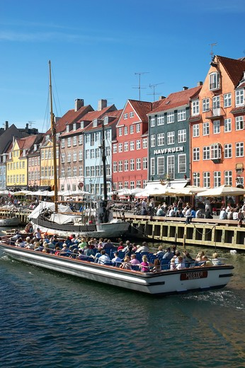 TOURIST TOUR BOAT MOORED SAILBOAT ANCIENT HOUSES AND WATERFRONT CAFE TERRACES NYHAVN NEW HARBOUR COPENHAGEN DENMARK : Stock Photo