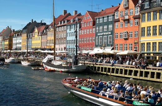 TOURIST TOUR BOAT MOORED SAILBOATS ANCIENT HOUSES AND WATERFRONT CAFE TERRACES NYHAVN NEW HARBOUR COPENHAGEN DENMARK : Stock Photo