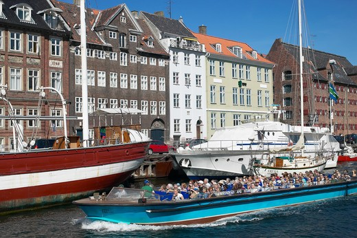 TOURIST TOUR BOAT MORRED BOATS AND ANCIENT HOUSES NYHAVN NEW HARBOUR COPENHAGEN DENMARK : Stock Photo