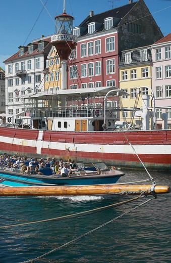 TOURIST TOUR BOAT LIGHTSHIP AND ANCIENT HOUSES NYHAVN NEW HARBOUR COPENHAGEN DENMARK : Stock Photo