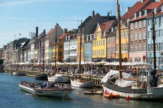 Stock Photo: 4285-9189 TOURIST TOUR BOAT MOORED SAILBOATS ANCIENT HOUSES AND WATERFRONT CAFE TERRACES  NYHAVN NEW HARBOUR COPENHAGEN DENMARK