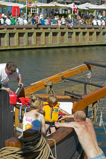 Stock Photo: 4285-9201 FAMILY GETTING READY FOR A BOAT TOUR AND WATERFRONT CAFE TERRACES NYHAVN HARBOUR COPENHAGEN DENMARK