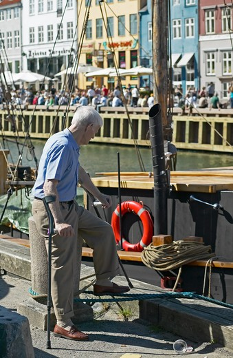 ELDERLY MAN WITH CRUTCHES MOORED SAILBOAT AND WATERFRONT CAFE TERRACES NYHAVN HARBOUR COPENHAGEN DENMARK : Stock Photo