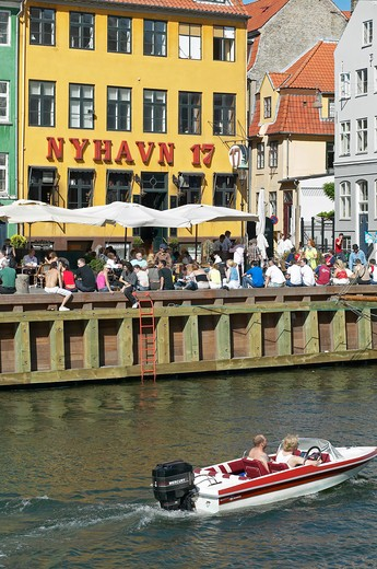 Stock Photo: 4285-9209 COUPLE IN MOTORBOAT ANCIENT HOUSE NYHAVN 17 AND WATERFRONT CAFE TERRACE NYHAVN NEW HARBOUR COPENHAGEN DENMARK