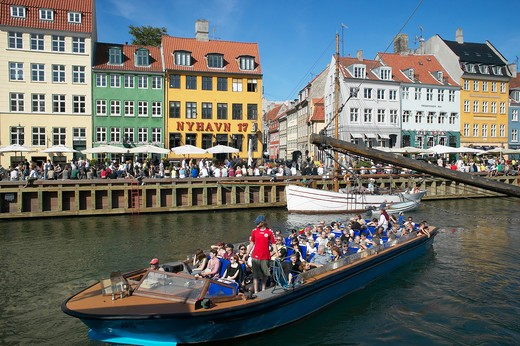 TOURIST TOUR BOAT ANCIENT HOUSES MOORED SAILBOAT AND WATERFRONT CAFE TERRACES NYHAVN NEW HARBOUR COPENHAGEN DENMARK : Stock Photo