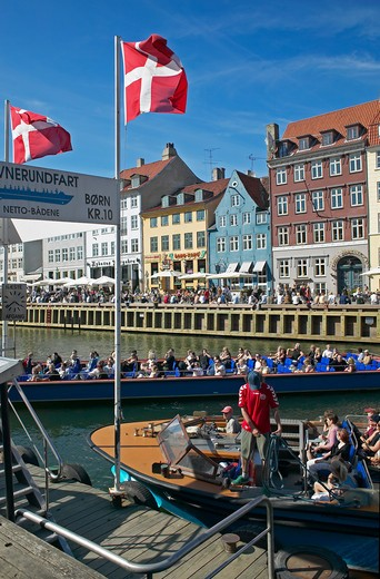 TOURIST TOUR BOATS DEPARTURE PIER ANCIENT HOUSES AND WATERFRONT CAFE TERRACES NYHAVN NEW HARBOUR COPENHAGEN DENMARK : Stock Photo