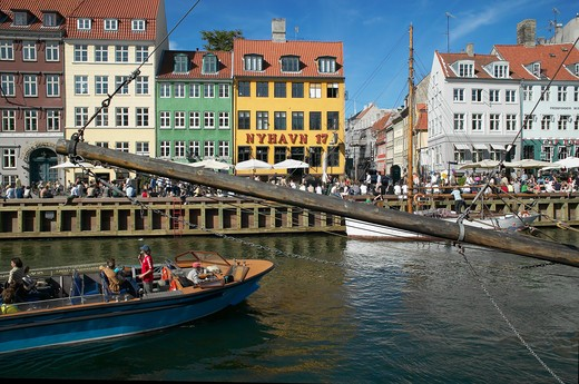 Stock Photo: 4285-9217 TOURIST TOUR BOAT MOORED SAILBOATS ANCIENT HOUSES AND WATERFRONT CAFE TERRACES NYHAVN NEW HARBOUR COPENHAGEN DENMARK