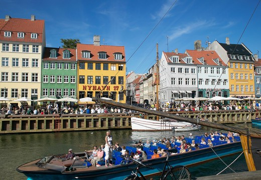 Stock Photo: 4285-9218 TOURIST TOUR BOAT MOORED SAILBOATS ANCIENT HOUSES AND WATERFRONT CAFE TERRACES NYHAVN NEW HARBOUR COPENHAGEN DENMARK