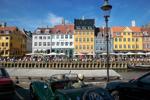 MAN IN CONVERTIBLE STREET LAMP ANCIENT HOUSES AND WATERFRONT CAFE TERRACES NYHAVN NEW HARBOUR COPENHAGEN DENMARK : Stock Photo