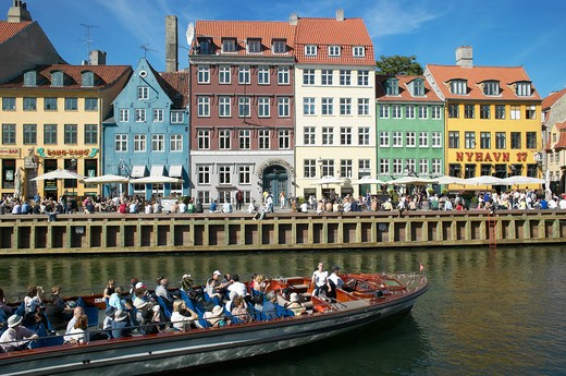 Stock Photo: 4285-9224 TOURIST TOUR BOAT ANCIENT HOUSES AND WATERFRONT CAFE TERRACES NYHAVN NEW HARBOUR COPENHAGEN DENMARK
