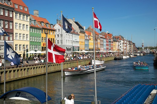 FLAGS TOURIST TOUR BOATS ANCIENT HOUSES AND WATERFRONT CAFE TERRACES NYHAVN NEW HARBOUR COPENHAGEN DENMARK : Stock Photo