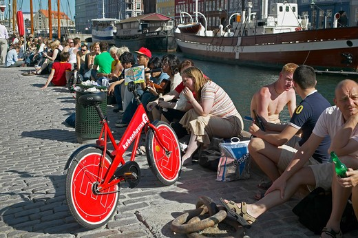 Stock Photo: 4285-9232 RED RENTED BIKE AND PEOPLE RELAXING ON WATERFRONT NYHAVN NEW HARBOUR COPENHAGEN DENMARK