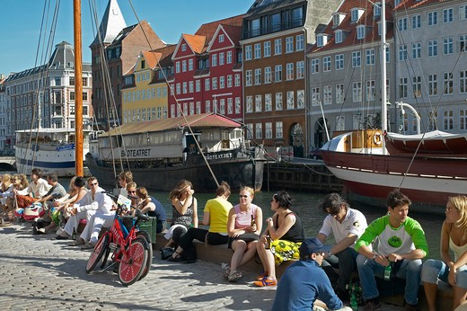 PEOPLE RELAXING ON WATERFRONT NYHAVN NEW HARBOUR COPENHAGEN DENMARK : Stock Photo