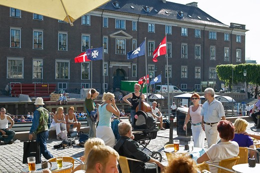 WATERFRONT CAFE TERRACE STREET MUSICIANS AND PEOPLE RELAXING NYHAVN NEW HARBOUR COPENHAGEN DENMARK : Stock Photo