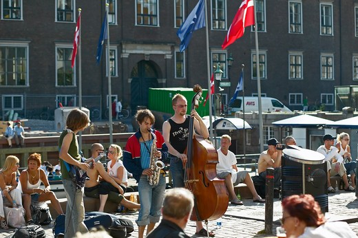 Stock Photo: 4285-9236 STREET MUSICIANS AND PEOPLE RELAXING ON WATERFRONT NYHAVN NEW HARBOUR COPENHAGEN DENMARK