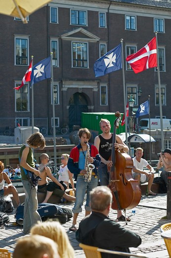 STREET MUSICIANS AND PEOPLE RELAXING ON WATERFRONT NYHAVN NEW HARBOUR COPENHAGEN DENMARK : Stock Photo