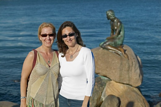 Stock Photo: 4285-9275 2 SPANISH YOUNG WOMEN IN FRONT OF THE LITTLE MERMAID BRONZE SCULPTURE BY EDWARD ERIKSEN ERECTED IN 1913 COPENHAGEN DENMARK