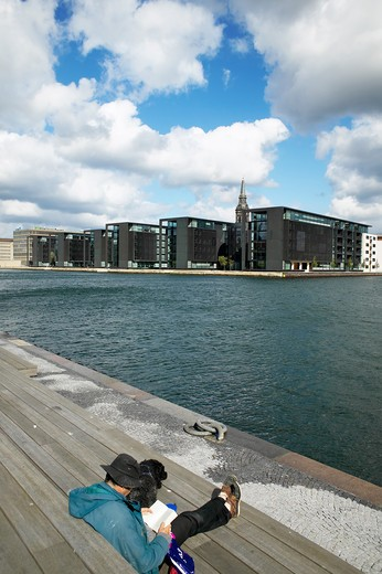 MAN READING ON PIER CANAL AND NORDEA BANK OFFICE BUILDINGS BUILT BY HENING LARSEN COPENHAGEN DENMARK : Stock Photo