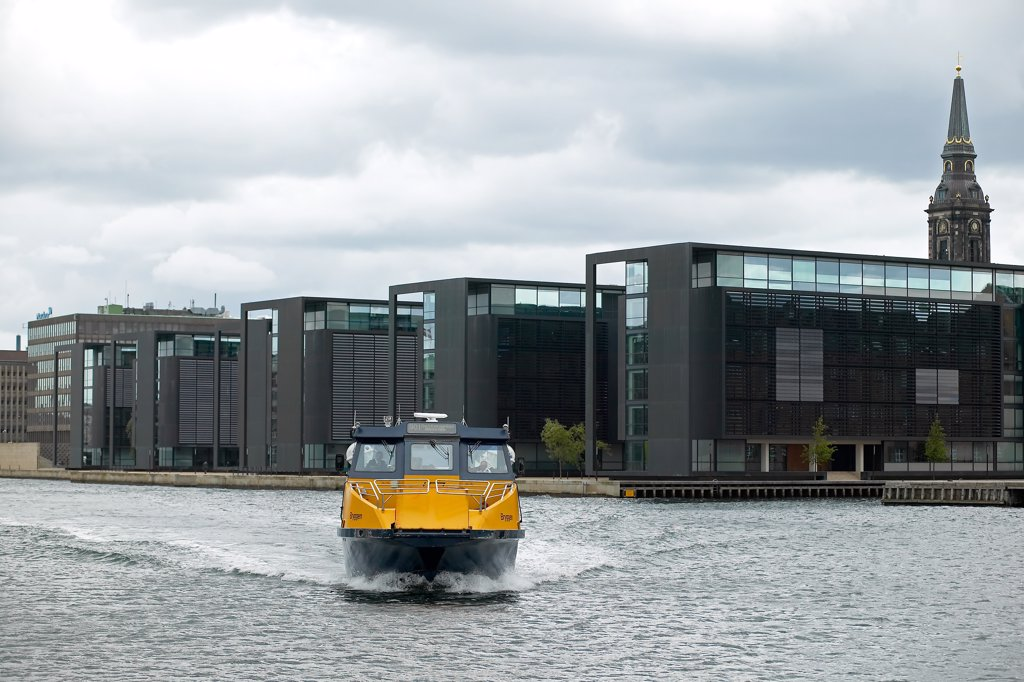YELLOW WATERBUS AND NORDEA BANK OFFICE BUILDINGS BUILT BY HENING LARSEN AND CHRISTIAN'S CHURCH COPENHAGEN DENMARK : Stock Photo