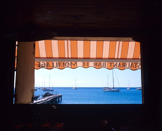 DESHAIES HARBOUR'S PONTOON AND RESTAURANT'S WINDOW WITH A BLUE SEA GUADELOUPE FRENCH WEST INDIES : Stock Photo